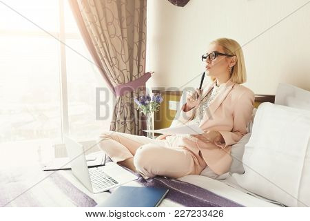 Serious Businesswoman Working With Documents. Female Professional In Hotel Examining Papers. Busines