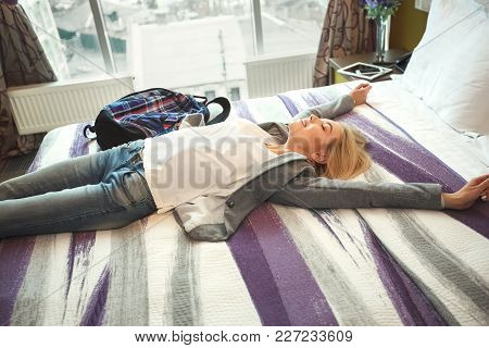 Above View Of Beautiful Young Woman Traveller Lying On Bed And Smiling After Hard Day, Copy Space