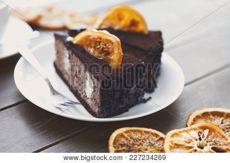 Chocolate Cake With Cream And Profiterole, Decorated With Candied Oranges. Traditional Creamy Desser
