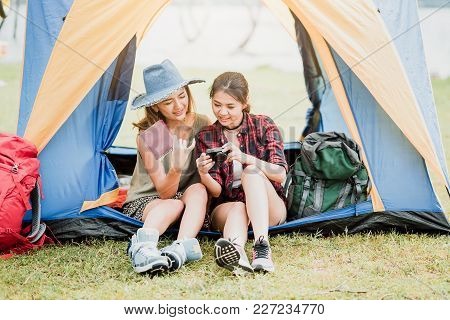 Two Happy Asian Woman Backpackers Checking Thier Photo In Camera Outside A Tent During Vacation Trip