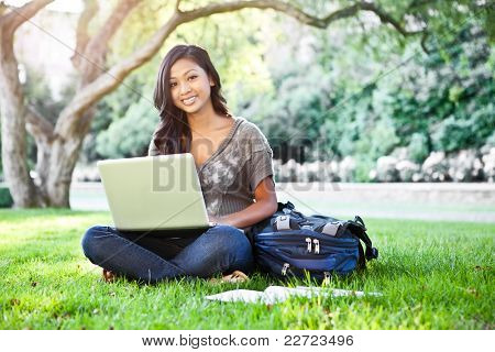 A shot of an Asian student working on laptop on campus
