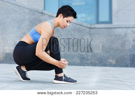Young Woman Tying Shoes Laces Before Running, Getting Ready For Jogging In Park, Closeup, Copy Space