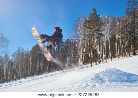 Portrait Of Young Man Performing Snowboarding Stunt Flying High In Air Against Clear Blue Sky On Mou