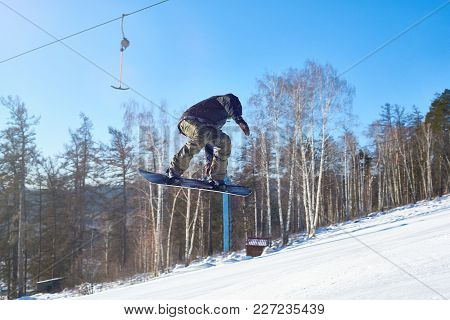 Portrait Of Young Man Performing Snowboarding Stunt Flying High In Air On Mountain Piste  At Ski Res