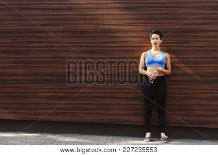 Young Woman Runner Is Having Break, Drinking Water While Jogging In City, Leaning At Dark Wooden Wal