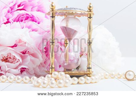 Vintage Hour Glass, Pearls And Fresh Peony Flowers On White Leather Background