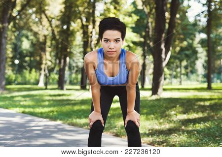 Tired Runner Breathing, Taking Run Break In Park. Athlete Woman With Hands On Knees Having Rest Afte