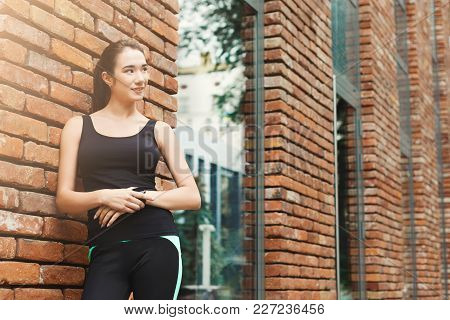 Young Sporty Woman Using Smart Watch, Standing At Brick Wall Background, Copy Space. Modern Technolo