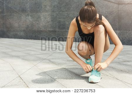 Woman Tying Shoelaces Before Running, Getting Ready For Workout Outdoors, Copy Space