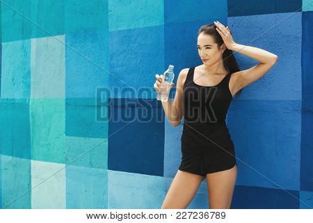 Young Woman Runner Is Having Break, Holding Bottle Of Water While Jogging In City, Bright Blue Wall