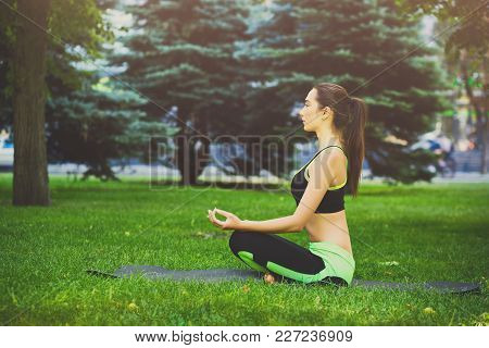 Young Woman Outdoors, Meditation Exercises. Girl Doing Lotus Pose For Relaxation. Wellness, Calmness