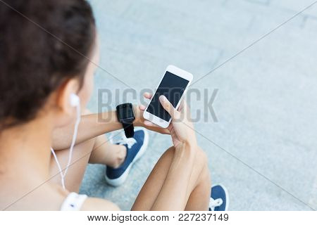 Image Of An African-american Woman Using Smartphone With Blank Screen Outdoors, While Listening To M
