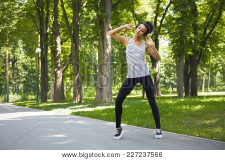 Pensive African-american Woman Posing In Sunny Summer Park, While Listening Music, Relaxing From Jog