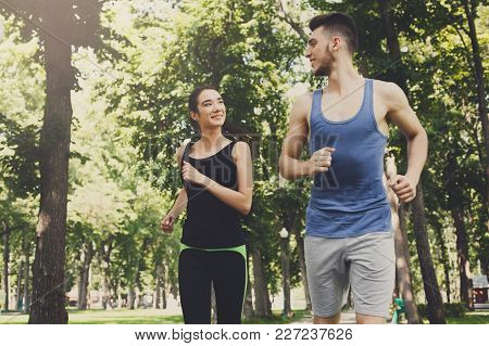 Young Sporty Woman And Man Jogging In Green Park During Morning Workout, Copy Space