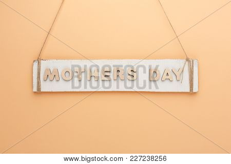 Mothers Day Background. Rustic Wooden Plank And Letters Hanging On Twine At Tender Peachy Backdrop,
