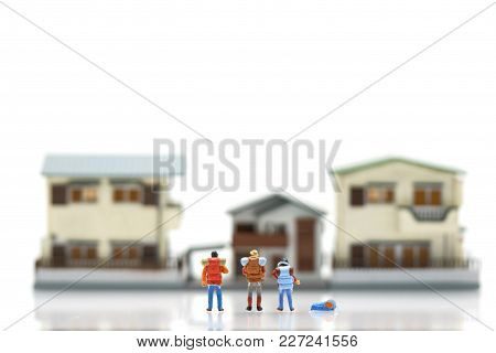 Miniature 3 People Stand On House And Hotel Models To Choose A Place To Live In. Using As Background