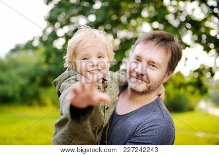 Middle Age Father With His Little Son Having Fun Together Outdoors. Happy Fatherhood Concept