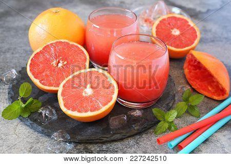 Fresh Grapefruit Pulp Juice In Two Glasses And Grapefruit Halves On Dark Background