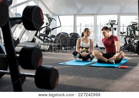 Full Length Portrait Of Young Sportive Couple Taking Break And Talking While Doing Yoga On Mats In M