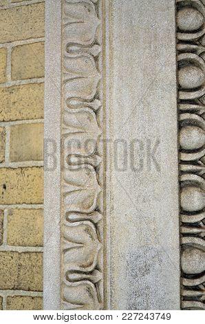 A Close Up Of Building Trim Against Brick