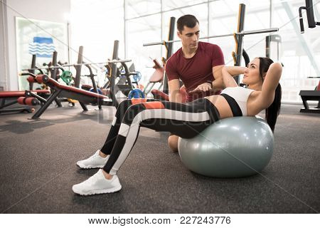Side View Portrait Of Muscular Coach Helping Young Woman Doing Exercises On Fitness Ball  In Modern