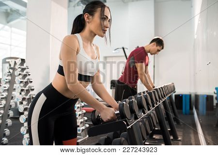 Side View Portrait Of Beautiful Young Woman Picking Up Dumbbells From Equipment Rack In Modern Gym,