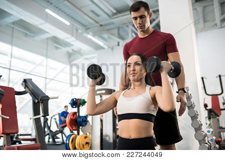 Waist Up Portrait Of Beautiful Young Woman Exercising With Dumbbells Sitting On Bench Helped By Pers