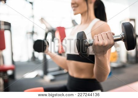 Close Up Of Sportive Young Woman  Training With Dumbbells In Modern Gym, Focus On Heavy Dumbbell In