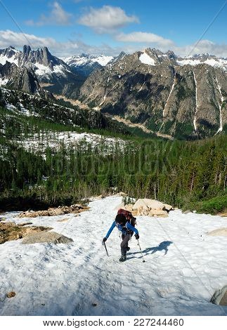 A Woman Climber Ascends Silver Star Mountain With The Liberty Bell Group And Washington Pass In The