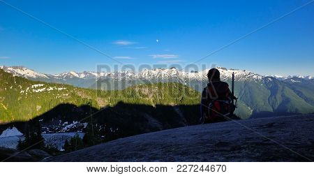 A Woman Hiker Enjoys Views Of The North Cascades Under A Full Moon. North Cascades National Park, Wa