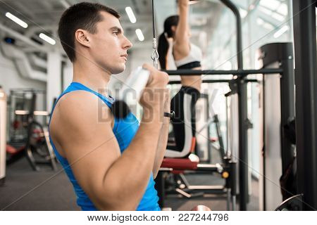 Side View Of Two People Exercising On Machines In Modern Gym By Window, Focus On Handsome Muscular M