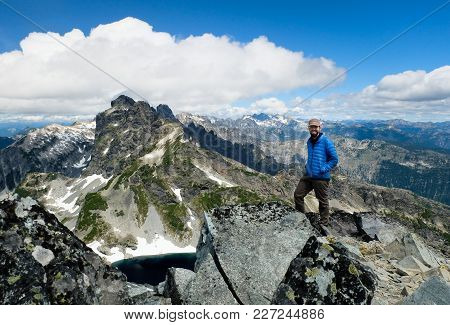 A Successful Climber On The Summit Of Chickamin Peak. Alpine Lakes Wilderness, Cascade Mountains, Wa
