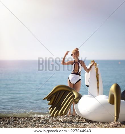 Young Pretty Fashion Woman Standing On Sea Shore Beach Near Resort Hotel With Huge Big Unicorn Float