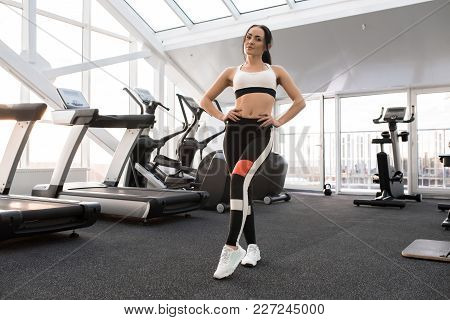 Full Length Portrait Of Fit Young Woman Wearing Sports Clothes Posing In Modern Gym Smiling Happily