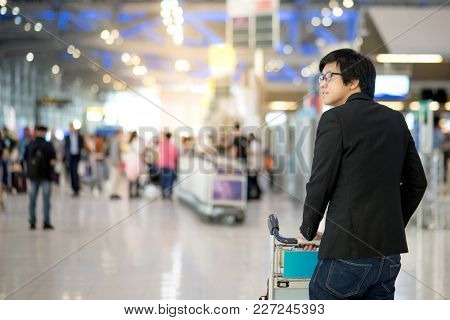 Young Asian Man With His Luggage On Airport Trolley Waiting For Check In At Airline Counter In The I