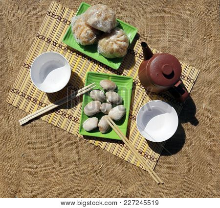 pork buns and steamed clams with green tea on a bamboo mat with chop sticks outdoors on burlap.