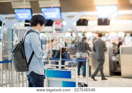 Young Asian Man Waiting For Check In And Dropping His Luggage At Airline Check-in Counter Of Interna