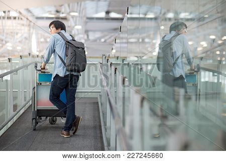 Young Asian Man Walking With Airport Trolley And His Suitcase Luggage In The International Airport T