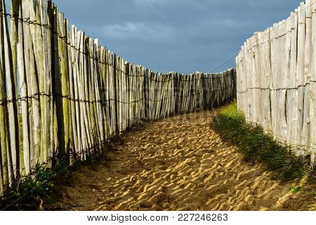 Coastal sandy trail, wooden fences on both side and dark cloudy sky, in Brittany, France