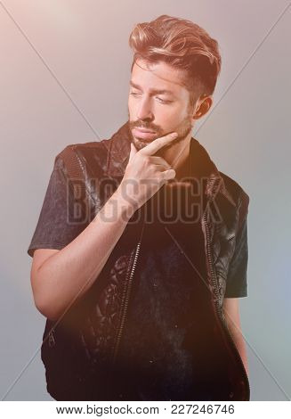 portrait of thinking stylish young man touch his beard