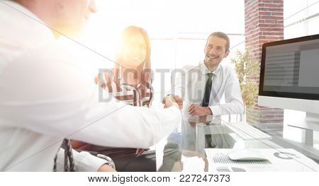 men shaking hands and smiling while sitting at the desk
