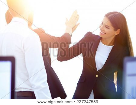 employees giving each other high five.