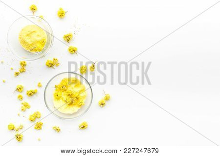 Aromatic Spa Salt. Yellow Spa Salt With Delicate Spring Flowers On White Background Top View.