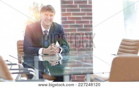Project manager sitting at a table in an empty conference room
