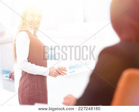 young business woman speaks at a discussion of financial project.