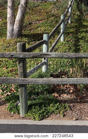 Corner Of A Two Rail Wooden Lodge Pole Fence System Where Two Sections Meet; One Borders A Paved Tra