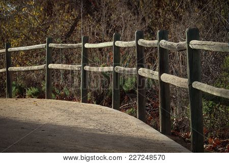 Two Rail Lodge Pole Fencing Along A Decomposed Granite Trail, Curving Around A Bend, The Sun Strikin