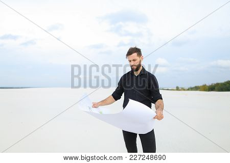 Investor Rent Land For New Amusement Park, Guy Come To Secluded Place With Plan. Young Man Unwrap Wh