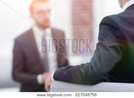 Image of young businessman communicating with his colleague
