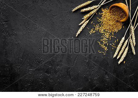 Raw Oat In Bowl Near Ears Of Wheat On Black Background Top View.